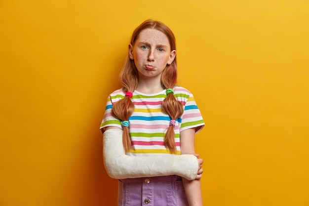 Photo of displeased small preteen girl has bad mood, purses lips and looks in discontent, being offended by close friend, has hurt feelings, dressed casually, poses with broken arm