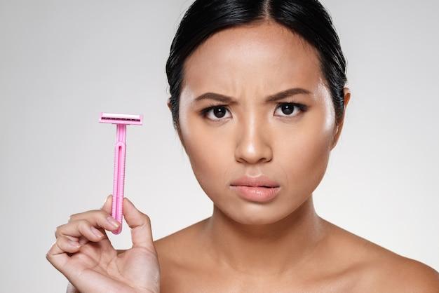 Photo of displeased woman showing razor