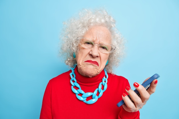 Photo of displeased wrinkled old curly woman holds mobile phone checks message frowns face wears spectacles red jumper and necklace