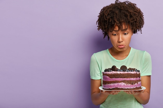 Photo of dissatisfied afro american woman holds plate of blueberry sweet cake, purses lower lip, has no good will, wants to eat delicious dessert but keeps to diet