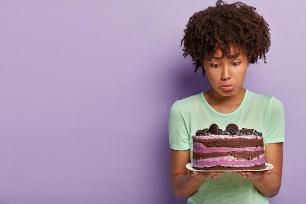 La foto di una donna afroamericana insoddisfatta tiene un piatto di torta dolce ai mirtilli, porta il labbro inferiore, non ha buona volontà, vuole mangiare un delizioso dessert ma si mantiene a dieta