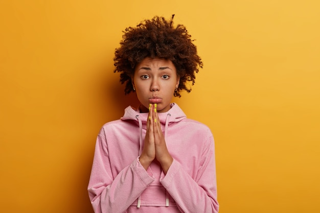 Photo of dissatisfied afro american woman keeps palms pressed together, prays or pleads, begs for your help, purses lips, looks sadly , poses against yellow wall, wears casual rosy hoodie