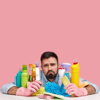 Photo of dissatisfied bearded man surrounded with cleaning agents, has sullen expression, wears protective gloves, feels tired