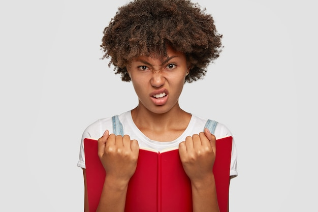 La foto di uno studente universitario insoddisfatto non ha alcun desiderio e non desidera studiare, tiene in mano il libro rosso, aggrotta le sopracciglia, si sente male e stanco di leggere, infastidito, modella su sfondo bianco. persone, concetto di apprendimento
