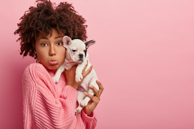 Photo of dissatisfied dark skinned woman owner of domestic animal, purses lower lip, sad her pet being ill, carries french bulldog puppy to vet