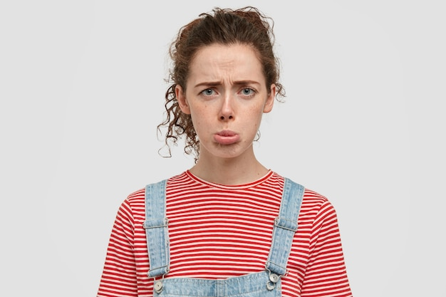 Photo of dissatisfied dejected woman purses lips, frowns face, has spoiled day at university