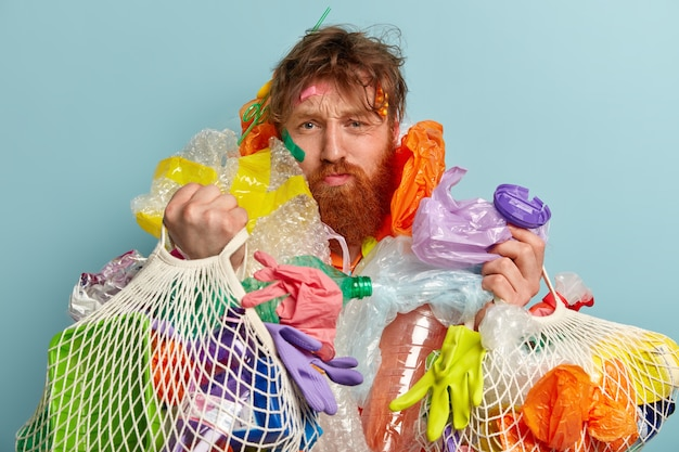 Photo of dissatisfied foxy bearded man sad after cleaning environment