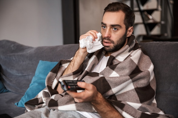 Photo of dissatisfied man 30s having temperature and being ill while sitting wrapped in blanket on sofa at home