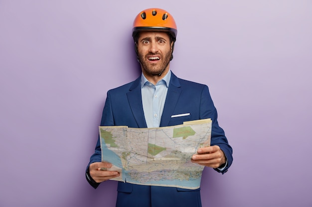 Photo of dissatisfied man builder director holds map, studies location for new construction, unhappy to choose not appropriate place, wears headgear and formal suit