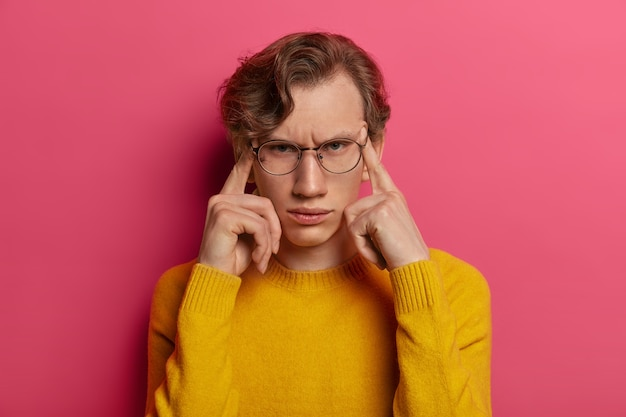 Photo of dissatisfied man suffers from headache, frowns face, touches temples with fingers, tries to focus, remembers something, wears spectacles, yellow sweater, isolated on pink wall