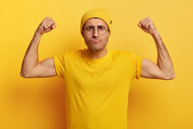 Foto di uomo insoddisfatto con espressione facciale arrabbiata, alza le mani, stringe i pugni