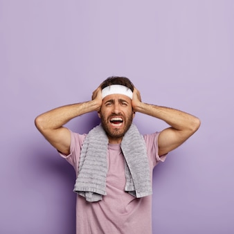 Photo of dissatisfied unshaven man keeps hands on head, suffers from headache, exercises indoor, dressed in casual t shirt, towel on shoulders, exhausted after training, being in low spirit.