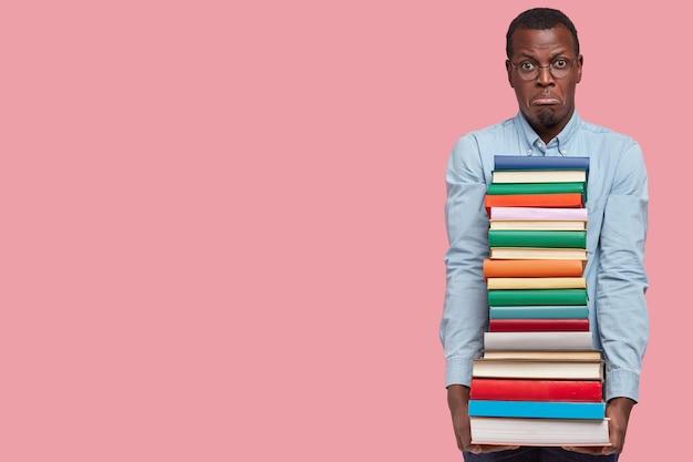 La foto del giovane uomo nero insoddisfatto tiene una pila di libri di testo, scontento di studiare, porta le labbra, indossa abiti formali