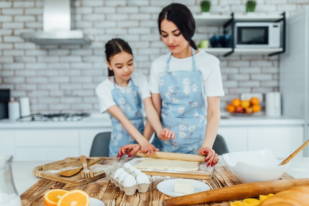 Photo of a dough and ingredients on kitchen table, and two girls cooking