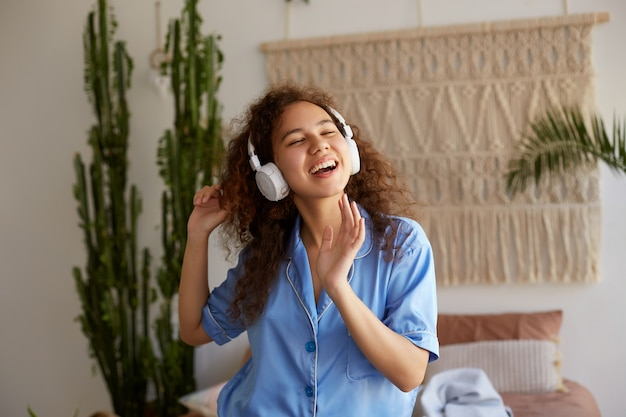 Photo of dreaming curly young nice african american lady, listening favorite music in headphones, sings a song and feels good.