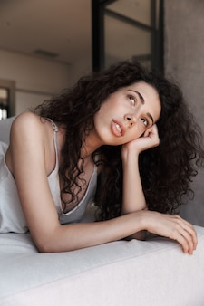 Photo of dreaming tender woman with long curly hair wearing silk leisure clothing looking aside with brooding glance, while propping up her head with hand on sofa