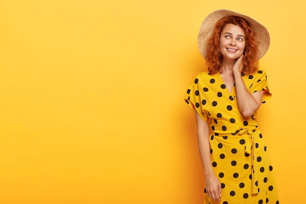 Photo of dreamy lovely redhead woman posing in yellow polka dress and straw hat