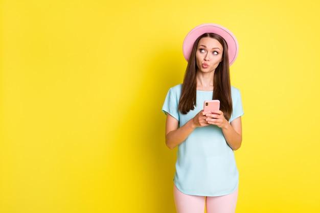 写真夢のような女の子のブロガーは携帯電話の外観を使用しますコピースペースは考えがソーシャルメディアの種類を決定すると思いますテキスト投稿着用ピンクブルーパンツズボン日よけ帽孤立した明るい輝き色の背景