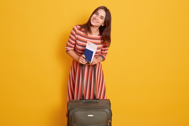 Photo of dreamy woman standing hear her suitcase and holding in her hands passport