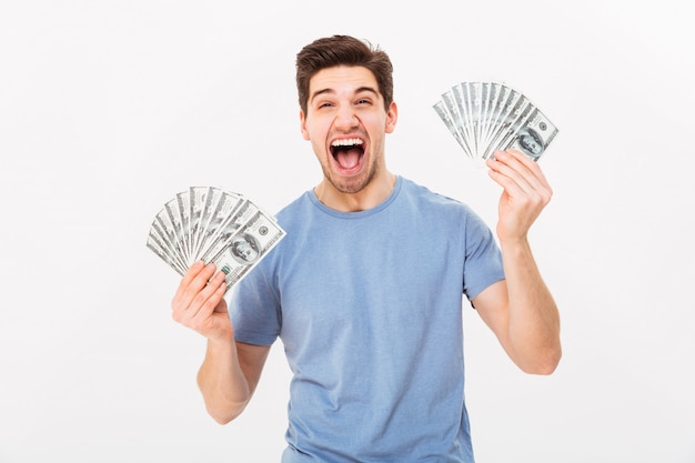 Photo of ecstatic man in casual t-shirt screaming and rejoicing his money prize in cash, isolated over white wall
