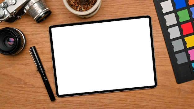 Photo editor office desk with tablet screen mockup colour checker camera on wooden background