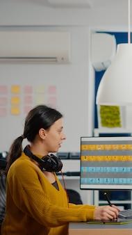 クリエイティブなオフィス環境でコンピューターに取り組んでいる写真編集スペシャリスト