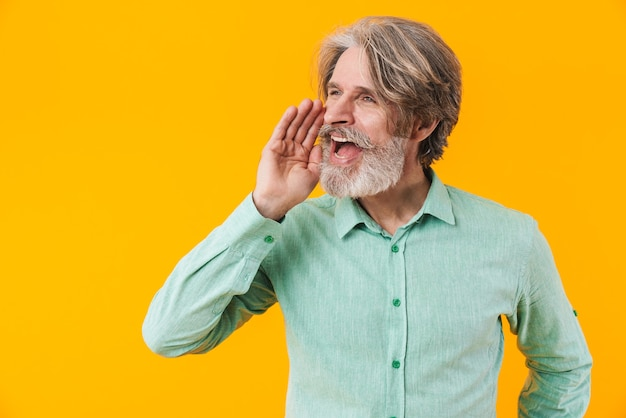Photo of elderly grey-haired bearded man in blue shirt posing isolated on yellow wall screaming.