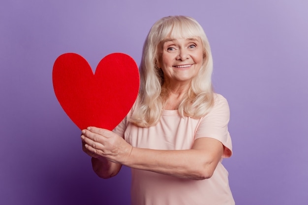 Photo of elderly woman hold big valentine card heart isolated on violet background