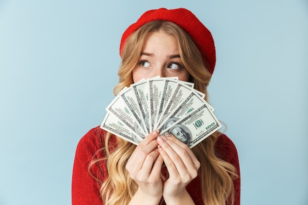 Photo of elegant blond woman 20s wearing red beret holding bunch of money banknotes isolated