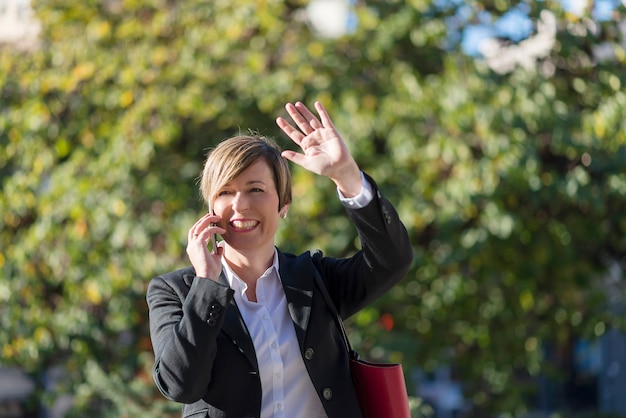 Photo of an elegant business woman smiling and talking on phone