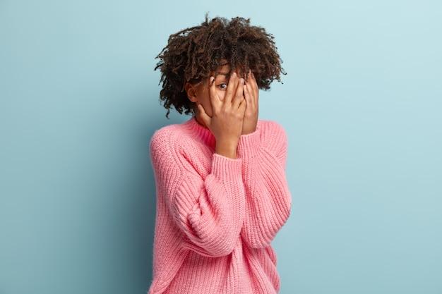 La foto del modello femminile impaurito e imbarazzato copre il viso con entrambe le mani, fa capolino tra le dita, osserva qualcosa di spaventoso