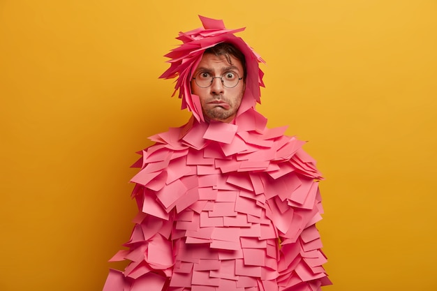 Photo of embarrassed nervous male advertiser bites lips, feels dissatisfied and tired, covered with pink sticky notes over body, poses indoor against yellow wall, has puzzled expression