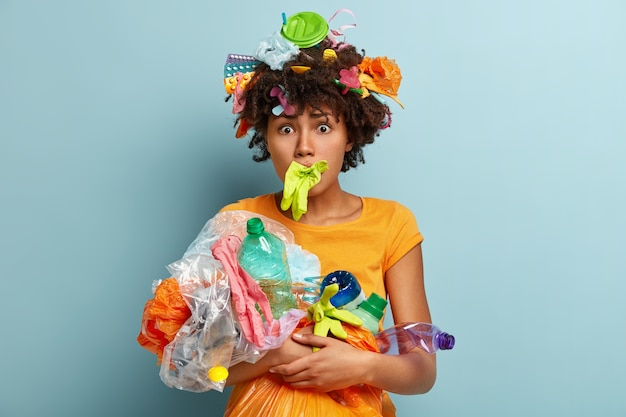 Photo of embarrassed young curly afro american woman has rubber glove in mouth, carries plastic garbage, worried by global environmental pollution, isolated on blue wall. ecology concept