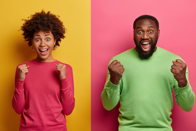 Photo of emotional dark skinned female and male clench fists, exclaim and support favorite football team, have overjoyed face expressions, dressed in casual wear, isolated on yellow and pink wall