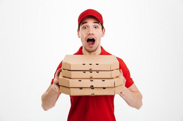Photo of emotional guy from delivery service in red t-shirt and cap holding stack of pizza boxes, isolated over white space