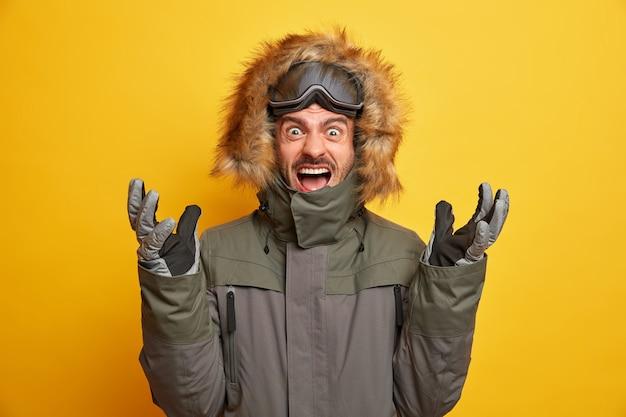 La foto dello snowboarder irritato emotivo alza le mani e grida esprime ad alta voce emozioni negative indossa giacca invernale con occhiali da sci guanti gesti mantiene attivamente la bocca aperta.