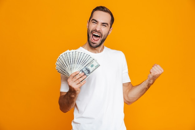 Photo of emotional man 30s in casual wear holding bunch of money, isolated