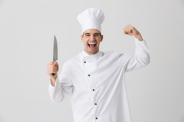 Photo of emotional screaming young man chef indoors isolated over white wall background holding knife showing biceps.