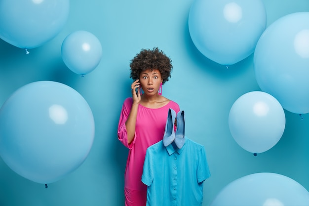 Photo of emotional stunned african american woman in pink evening dress, surrounded by festive balloons, shocked to hear stunning news, holds shirt on hanger and blue shoes, dresses for celebration