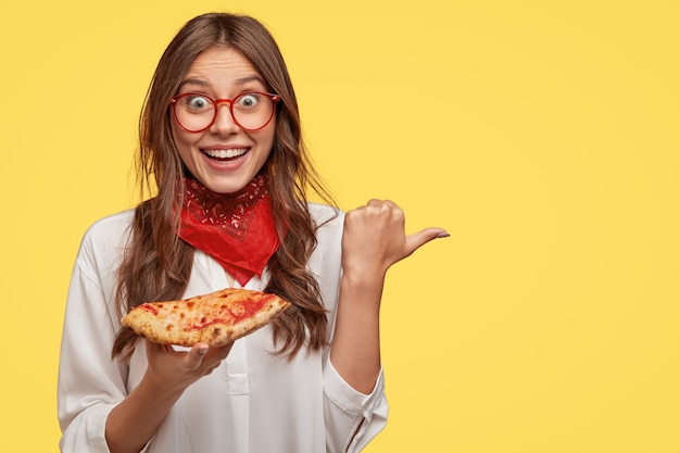 Photo of emotive surprised brunette lady with toothy smile, wears red bandana, holds slice of pizza, points with thumb aside, models against yellow wall for your advertising content. tasty dish