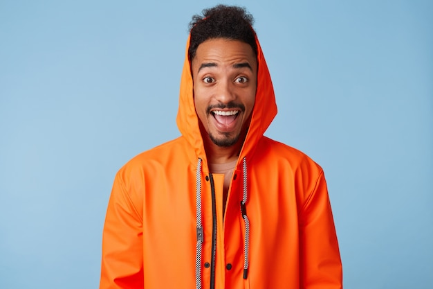 Photo of enthusiastic young african american dark skinned guy in orange rain coat, smiles broadly and looks with wide open mouth, stands.