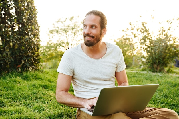 Photo of european beautiful man in white t-shirt sitting on grass in green park and working on silver notebook