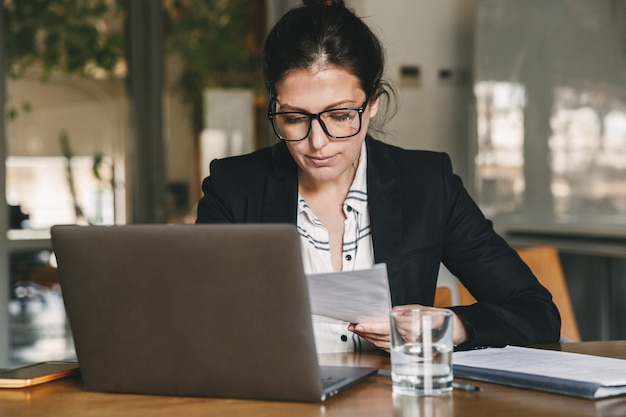Photo of european businesswoman 30s wearing formal clothing and eyeglasses working in office on laptop and examining paper documents, while holding in hand