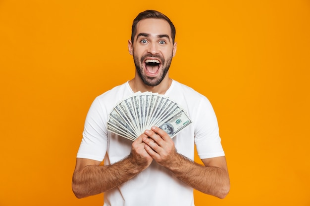 Photo of european man 30s in casual wear holding bunch of money, isolated