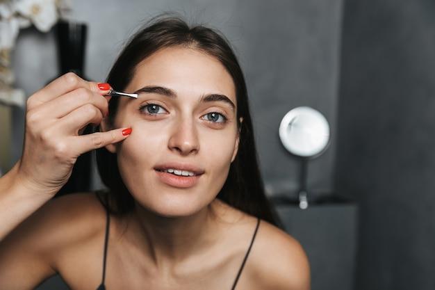 Photo of european woman 20s with long dark hair standing in bathroom