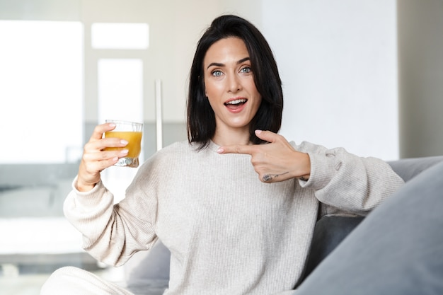 Photo of european woman 30s drinking orange juice, while sitting on sofa in bright room