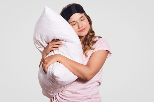 Photo of european woman with healthy skin leans on soft pillow, wears pyjamas, eyewear on head, poses alone on white, has sleepy look. people, good morning concept