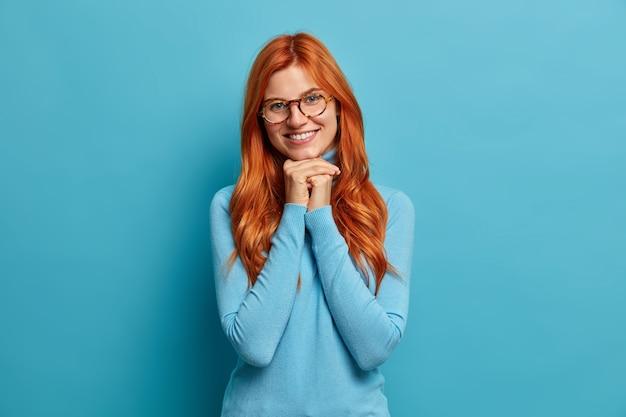 La foto di una donna europea con i capelli rossi tiene le mani sotto il mento esprime emozioni positive, indossa occhiali da vista e dolcevita casual.