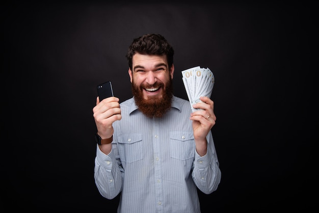 Photo of excited bearded guy, holding a smartphone and a lot of money, celebrating his won over drak isolated background