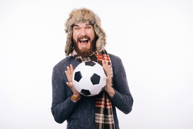 Photo of excited bearded guy wearing a cozy winter hat, holding soccer ball, and amazed looking at camera